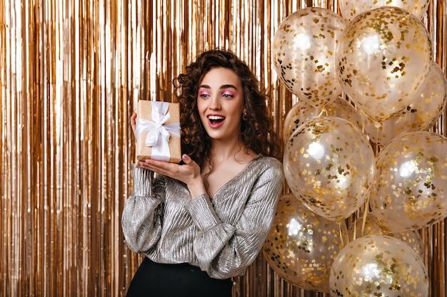 Mujer joven en blusa plateada posando felizmente con caja de regalo
