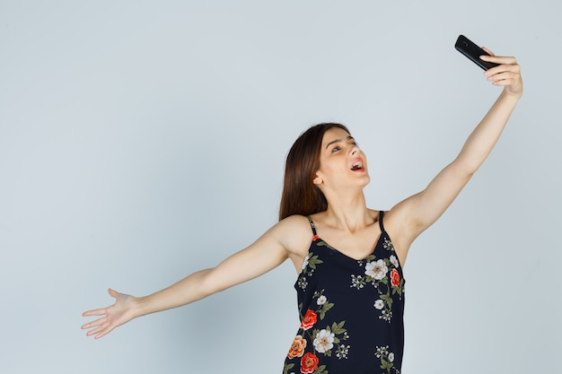 Mujer joven en blusa posando mientras toma selfie en teléfono inteligente y mirando relajado, vista frontal.