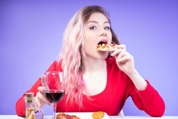Mujer joven en blusa roja come pizza y sostiene una copa de vino tinto