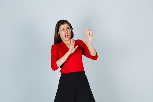 Mujer joven en blusa roja, falda negra mostrando gesto de restricción y mirando asustado