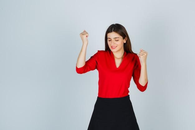 Mujer joven en blusa roja, falda negra que muestra el gesto del ganador y parece afortunado