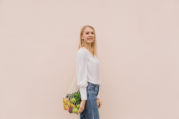 Mujer joven con bolsa de compras de cadena con frutas sobre un fondo beige.