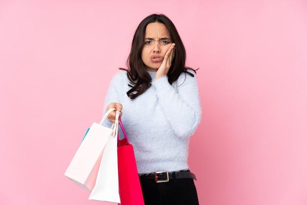 Mujer joven con bolsa de compras con dolor de muelas