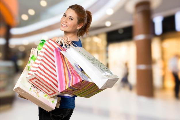 Mujer joven con bolsa de compras en el fondo del centro comercial borrosa