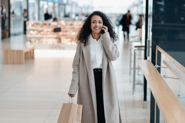 Mujer joven con una bolsa de compras hablando por un teléfono inteligente