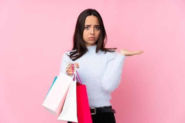 Mujer joven con bolsa de compras sobre pared rosa aislado infeliz por no entender algo