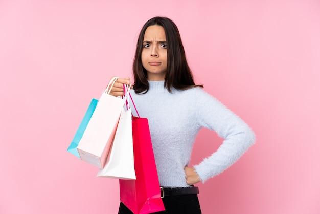 Mujer joven con bolsa de compras sobre pared rosa enojado
