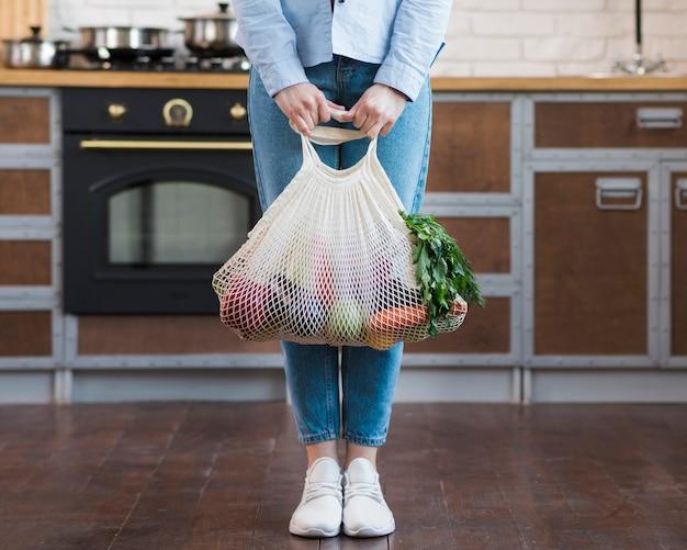 Mujer joven con bolsa ecológica con comestibles orgánicos