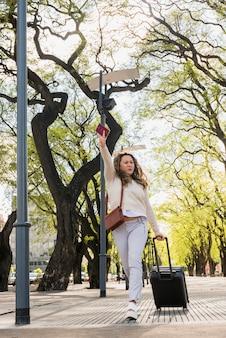Mujer joven con bolsa de equipaje un pasaporte caminando apresuradamente para llamar un taxi