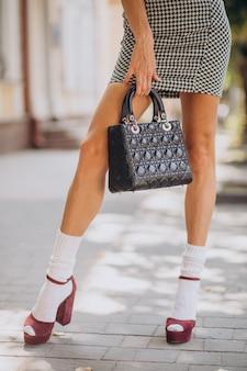 Mujer joven con bolsa fuera de la calle