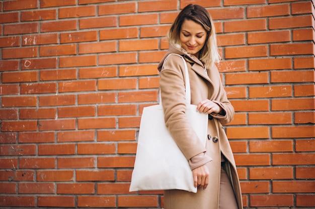 Mujer joven con bolsa junto a la pared de ladrillo