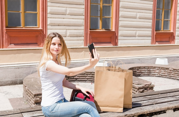 Mujer joven con bolsa de papel tomando selfie con teléfono móvil