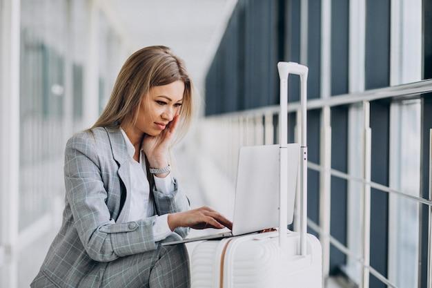 Mujer joven con bolsa de viaje, reservar un vuelo en la computadora portátil en el aeropuerto