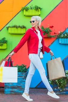 Mujer joven con bolsas cerca de pared colorido