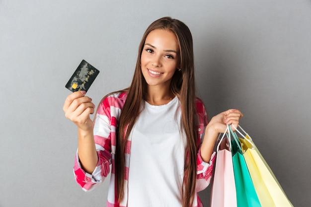 Mujer joven con bolsas de compra y tarjeta de crédito