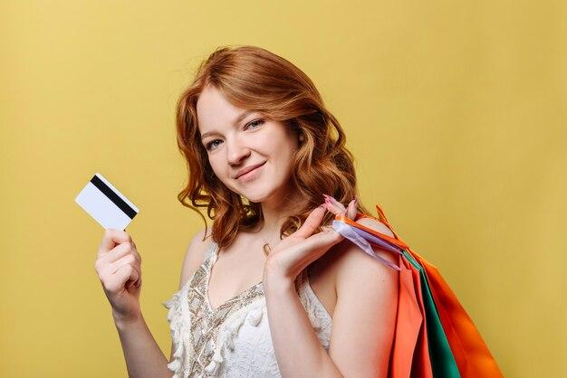 Mujer joven con bolsas de compra y una tarjeta de crédito