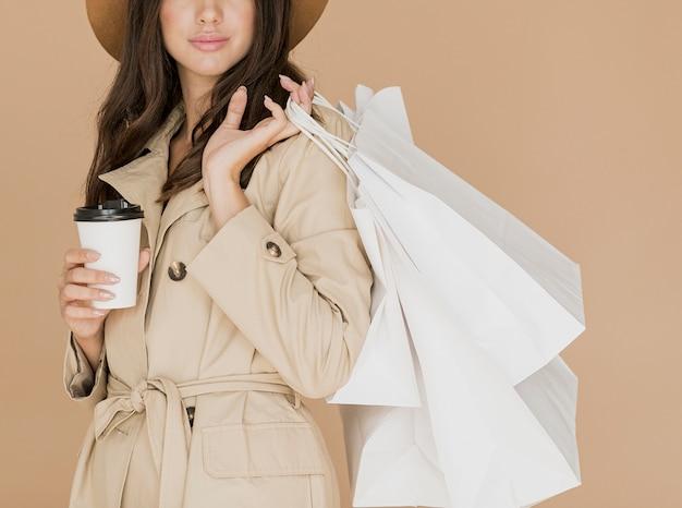Mujer joven con bolsas de compras y café