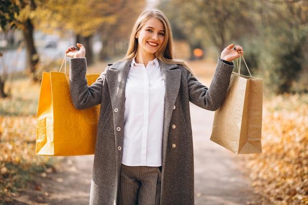 Mujer joven con bolsas de compras caminando en el parque