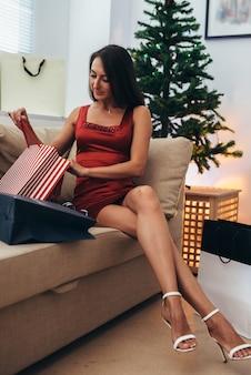 Mujer joven con bolsas de compras cerca del árbol de navidad.