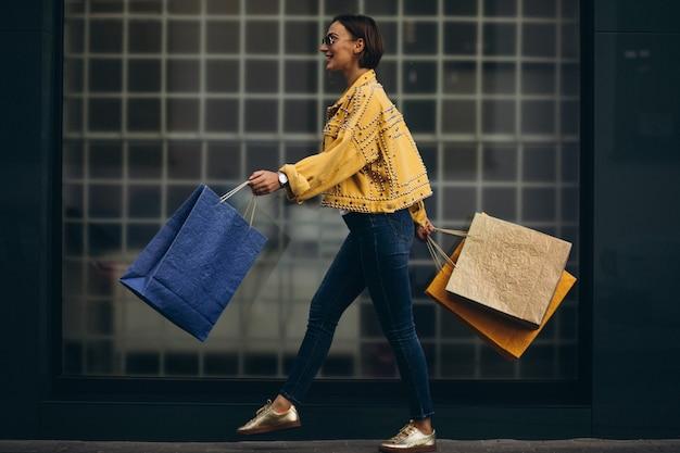 Mujer joven con bolsas de compras en la ciudad