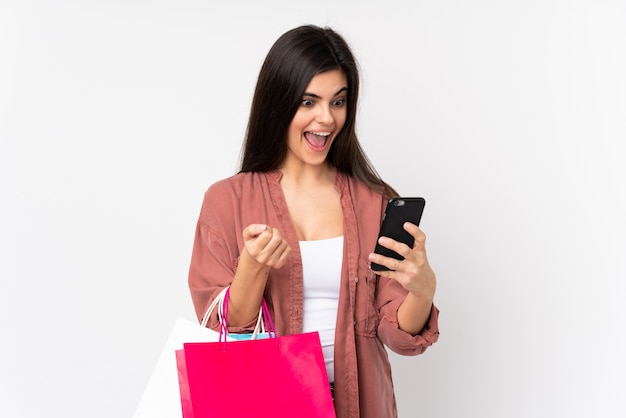 Mujer joven con bolsas de compras y escribir un mensaje con su teléfono celular a un amigo