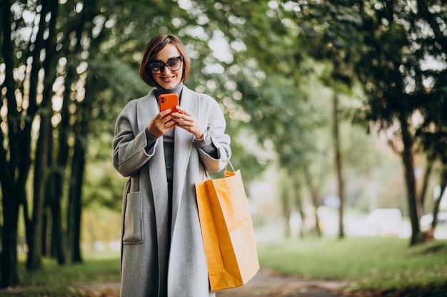 Mujer joven, con, bolsas de compras, en el estacionamiento