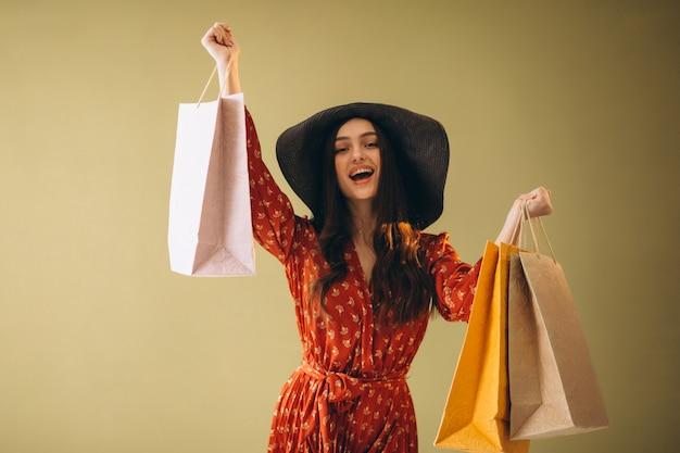 Mujer joven con bolsas de compras en un hermoso vestido y sombrero