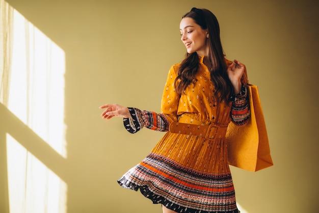 Mujer joven con bolsas de compras en un hermoso vestido
