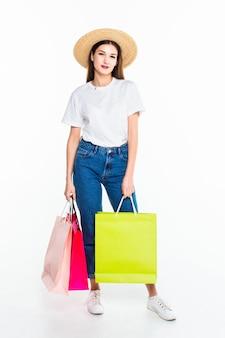 Mujer joven con bolsas de compras en la pared blanca