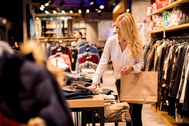 Mujer joven con bolsas de compras de pie en la tienda de ropa