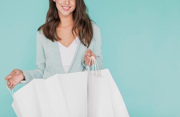 Mujer joven con bolsas de compras sobre fondo azul