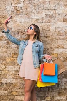Mujer joven con bolsas de compras tomando selfie