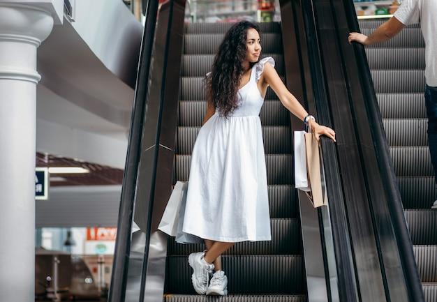 Mujer joven con bolsas en una escalera mecánica