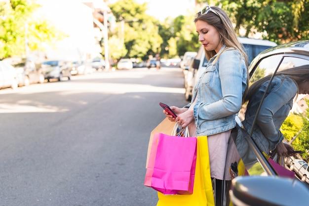 Mujer joven con los bolsos de compras brillantes usando smartphone en el coche