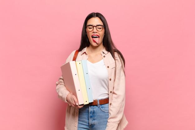 Mujer joven y bonita con actitud alegre, despreocupada y rebelde, bromeando y sacando la lengua, divirtiéndose. concepto de estudiante