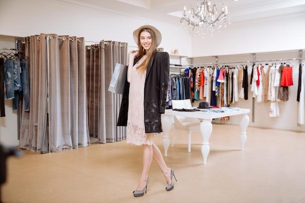 Mujer joven y bonita alegre con bolsas de la compra de pie y sonriendo en la sala de exposición