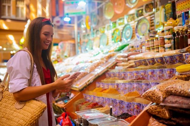 Una mujer joven y bonita eligiendo productos en una tienda y mirando involucrado