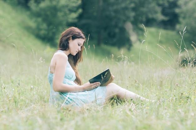 Mujer joven y bonita con un libro sentado sobre la hierba verde. foto con espacio de copia