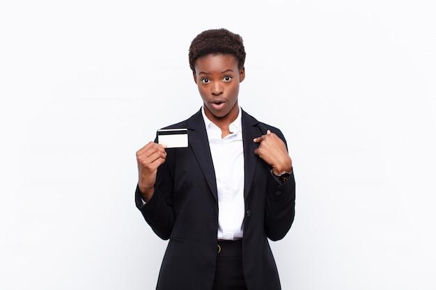 Mujer joven y bonita negra que se siente feliz, sorprendida y orgullosa, apuntando a sí misma con una mirada emocionada y asombrada con una tarjeta de crédito