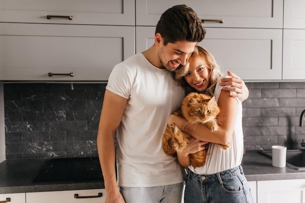 Mujer joven y bonita que sostiene el gato durante el retrato familiar. lindo hombre morena abrazando a su esposa.