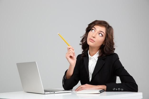 Mujer joven bonita rizada concentrada pensativa en la planificación de la chaqueta negra usando la computadora portátil y el cuaderno