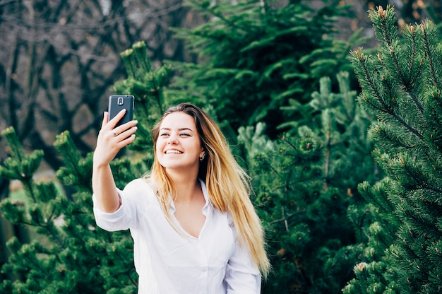 Una mujer joven y bonita sonriendo y haciendo selfie en un parque