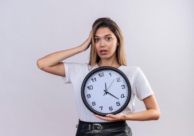Una mujer joven y bonita sorprendida en camiseta blanca manteniendo la mano en la cabeza mientras sostiene el reloj de pared