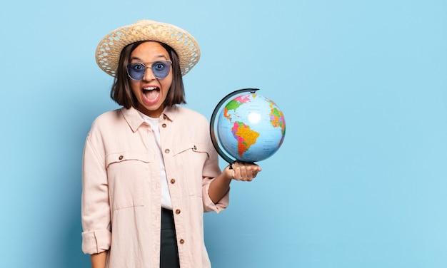 Mujer joven bonita viajera con un mapa del mundo