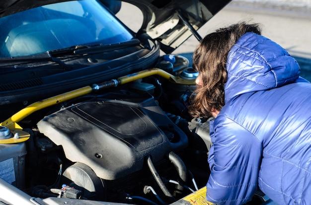 Mujer joven en un borde de la carretera cerca del coche roto con el capó abierto