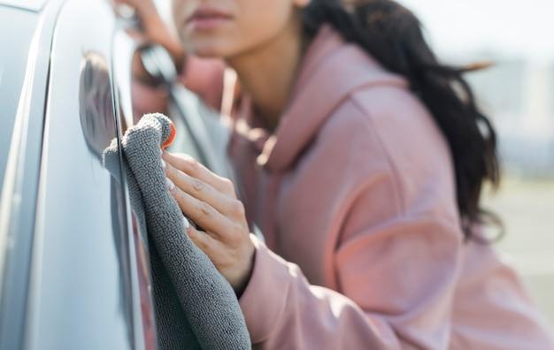 Mujer joven borrosa que limpia el coche
