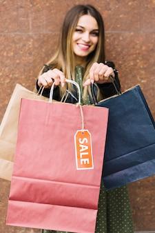 Mujer joven borrosa que muestra los bolsos de compras coloridos con la etiqueta de la venta