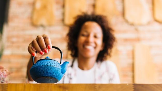 Mujer joven borrosa que sostiene la caldera azul en la mano