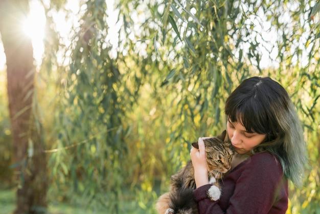 Mujer joven en el bosque que sostiene su gato de gato atigrado encantador