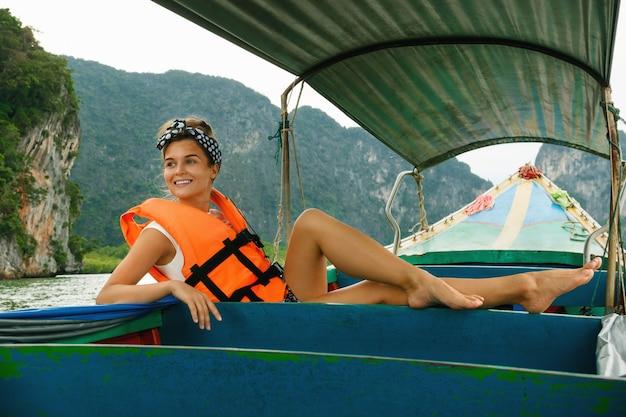 Mujer joven en el bote de cola larga durante sus vacaciones en tailandia